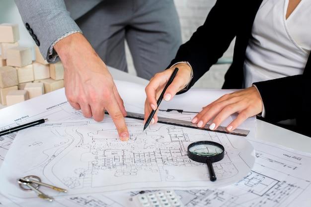 Teammitglieder, die einen architekturplan analysieren Kostenlose Fotos