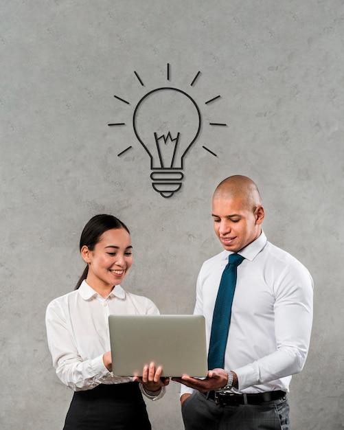 Teammitglieder, die einen laptop betrachten Premium Fotos