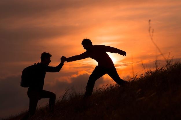 Teamwork paar wandern helfen sich gegenseitig vertrauen unterstützung silhouette in bergen, sonnenuntergang. Premium Fotos
