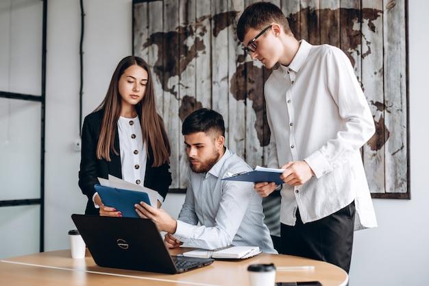 Teamwork-prozess junge unternehmerarbeit mit neuem startprojekt im büro frau, die papier in den händen hält, bärtiger mann sehen es. Premium Fotos