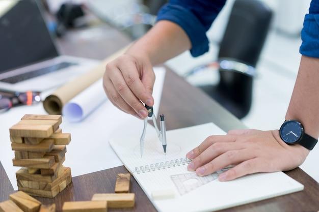 Technik mann hand mit kompass für die zeichnung plan design der bauarbeiten an der skizze Premium Fotos