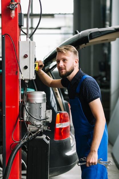 Techniker, der ausrüstung an der garage verwendet Kostenlose Fotos