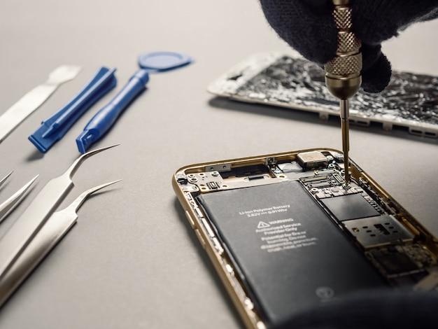 Techniker, der defekten smartphone auf schreibtisch repariert Premium Fotos