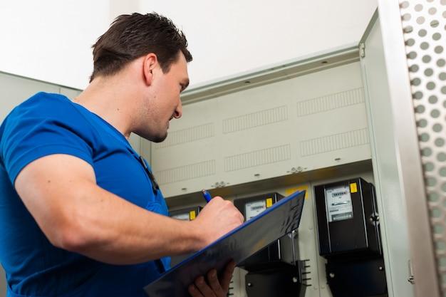 Techniker, der den stromzähler liest Premium Fotos