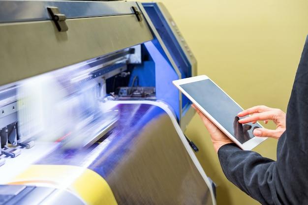 Techniker, der die tablet-steuerung mit großem tintenstrahldruck auf blauem vinyl verwendet Premium Fotos