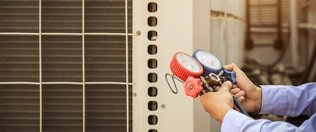Techniker, der einen verteiler zum befüllen von industrieklimageräten verwendet. Premium Fotos