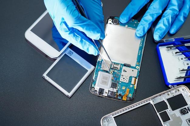 Techniker, der mikroschaltungshauptplatine von smartphone repariert. Premium Fotos