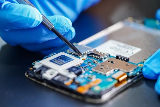Techniker, der mikroschaltungshauptplatine von smartphone repariert Premium Fotos