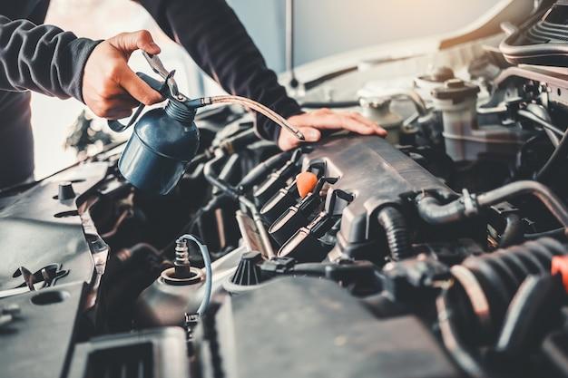 Techniker hands des automechanikers arbeitend in der autoreparatur Premium Fotos