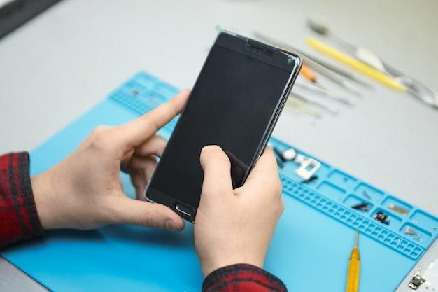 Techniker mit kariertem hemd, der an seinem arbeitsplatz sitzt und das smartphone in seinen händen einschaltet, um fehler zu finden Kostenlose Fotos