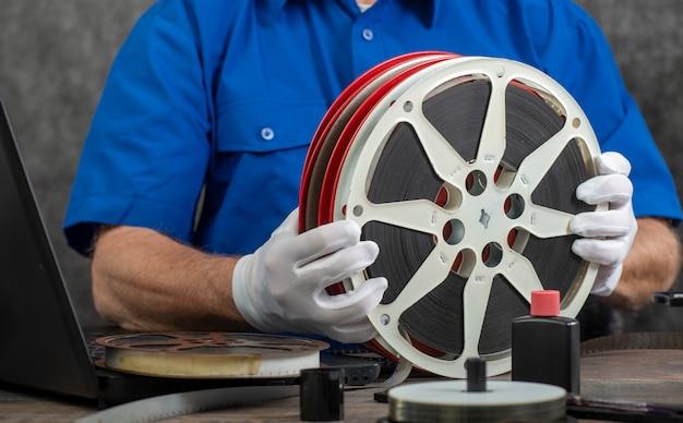 Techniker mit weißen handschuhen, die alten film 16mm digitalisieren Premium Fotos