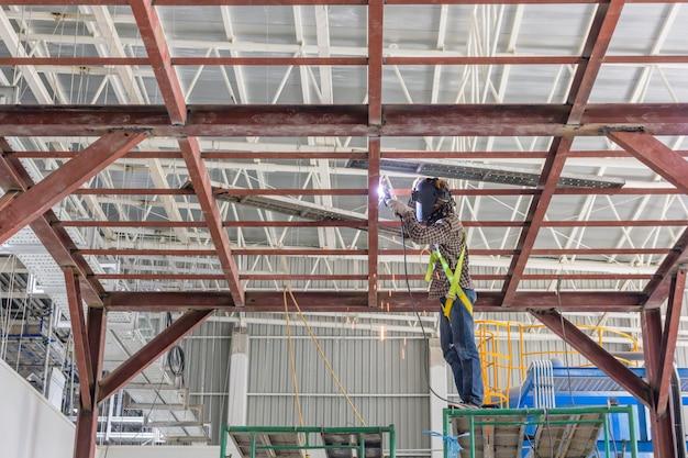 Techniker schweißen stahlkonstruktion. baustellebild für den hintergrund. Premium Fotos