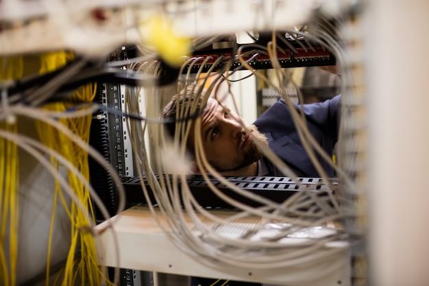 Techniker überprüft kabel in einem rack-server Premium Fotos