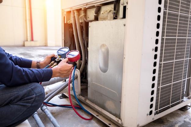 Techniker überprüft klimaanlagenmessgerät auf das füllen von klimaanlagen. Premium Fotos