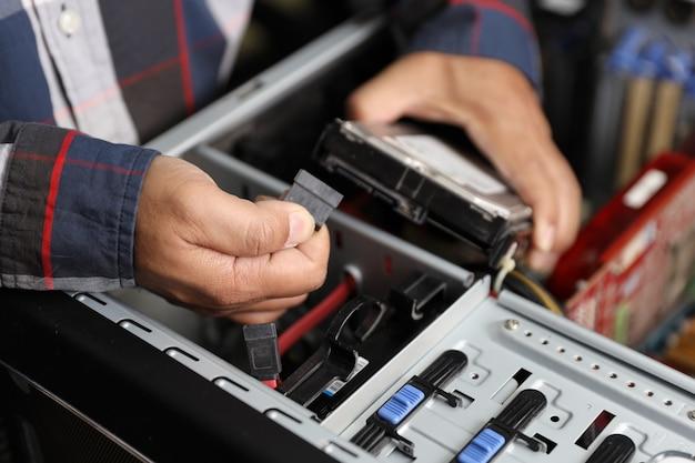 Technikermannverlegenheit oder -verbesserung der festplatte durch ziehen sie heraus oder schließen sie kabel am computer an Premium Fotos