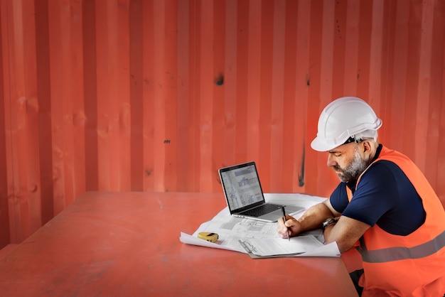 Technikkerl, der an dem projekt an der baustelle arbeitet Kostenlose Fotos