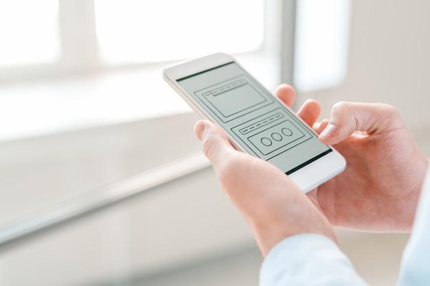 Technische schemata in smartphones von jungen geschäftsleuten gehalten, die durch sie scrollen und analysieren Premium Fotos