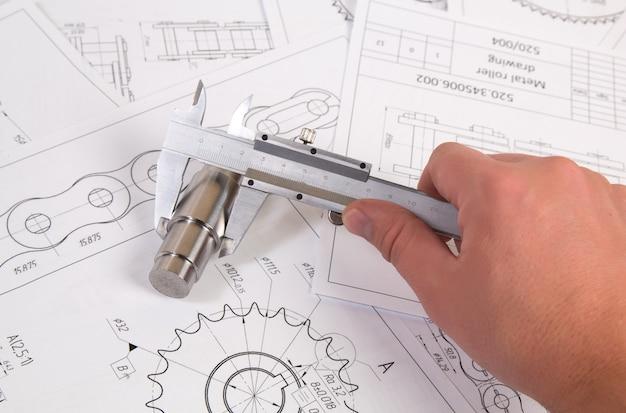 Technische zeichnung, bremssattel und antriebsrollenkette. ingenieurwesen, technologie und metallverarbeitung. schiebermessung des details der industriekette. Premium Fotos
