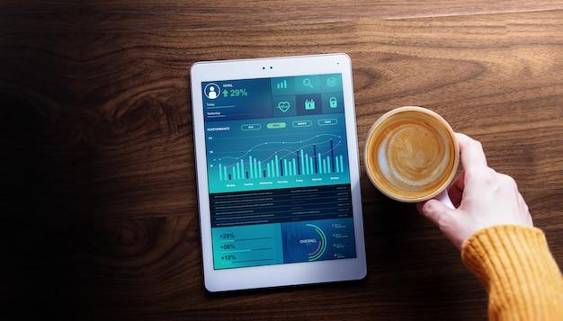 Technologie-, finanz- und geschäftsmarketing im alltagsleben-konzept. frau mit dem heißen kaffee, der diagramme und diagramme sieht, stellen auf digital-tablet dar. ansicht von oben Premium Fotos