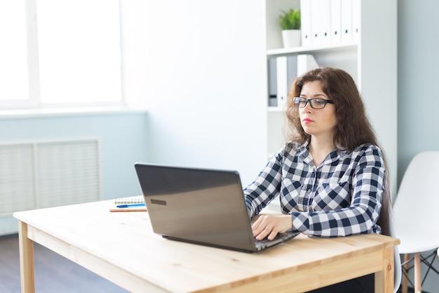 Technologie-, geschäfts- und personenkonzept - ernsthafte frau in der brille, die am computer im büro arbeitet. Premium Fotos