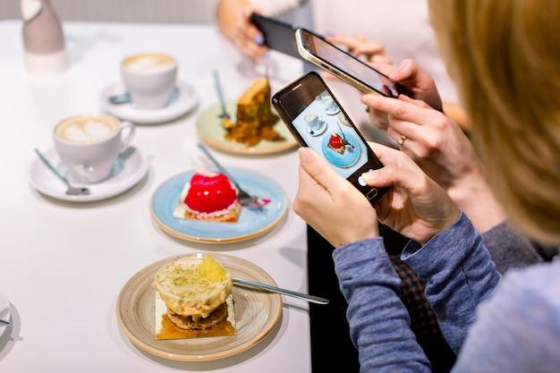 Technologie-, lebensstil-, freundschafts- und leutekonzept - drei glückliche junge frauen mit den smartphones, die zuhause fotos von ihren kaffeetassen und nachtischen am café machen Premium Fotos