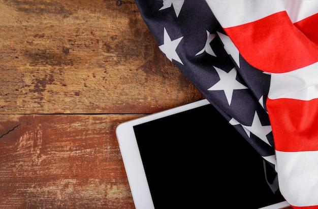 Technologie, patriotismus, jahrestag, nationalfeiertage der tablette an der amerikanischen flagge und unabhängigkeitstag Premium Fotos