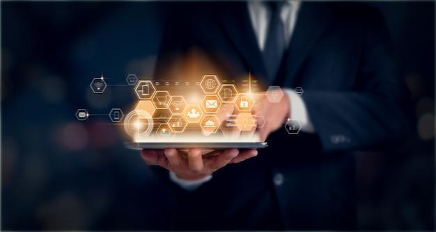 Technologieinnovationskonzept, geschäftsmann, der tablette hält und drücken digital mit gemischten medien. Premium Fotos