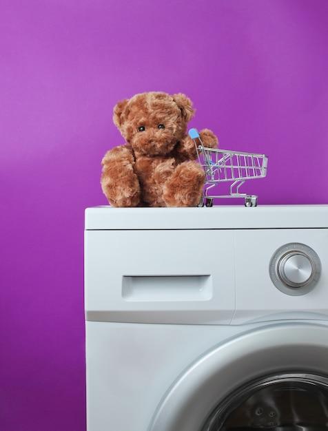 Teddybär mit einkaufswagen auf einer waschmaschine Premium Fotos