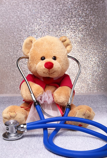 Teddybär und stethoskop auf weiß Premium Fotos