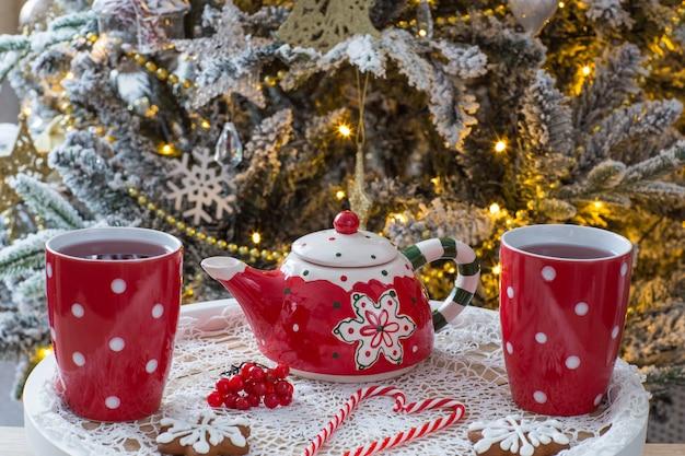 Tee in tassen, eine teekanne, lebkuchen und süßigkeiten Premium Fotos
