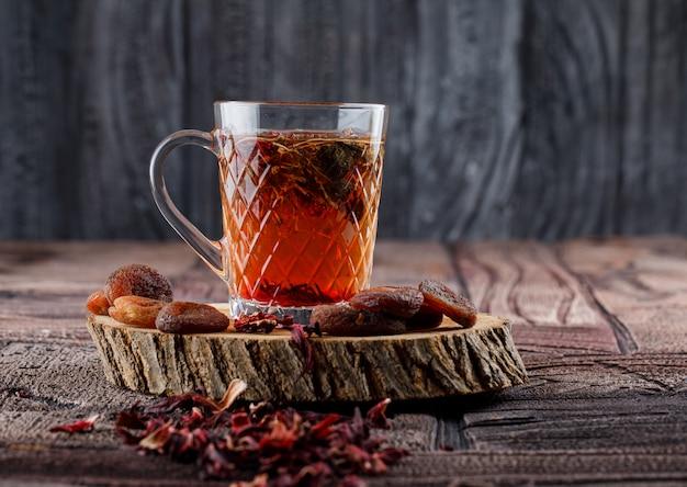 Tee mit getrockneten früchten und blumen, zitrone auf holz in einer tasse auf steinfliesen und holzoberfläche Kostenlose Fotos