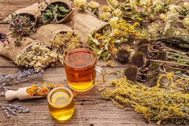 Tee mit honig. kräutererntesammlung und blumensträuße von wildkräutern. alternative medizin. natürliche apotheke, self-care-konzept Premium Fotos