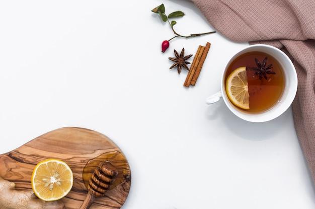 Tee mit zitrone nahe brett mit honigschöpflöffel Kostenlose Fotos