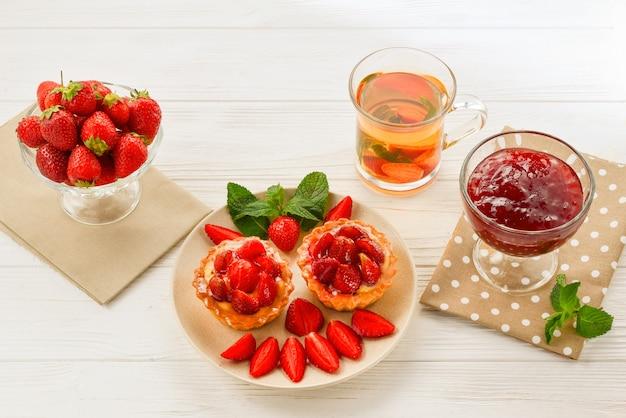 Tee trinken mit törtchen und kuchen mit erdbeeren Premium Fotos