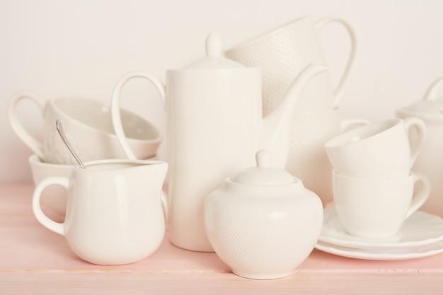 Tee- und kaffeesatz auf dem tisch auf einem weißen hintergrund Premium Fotos