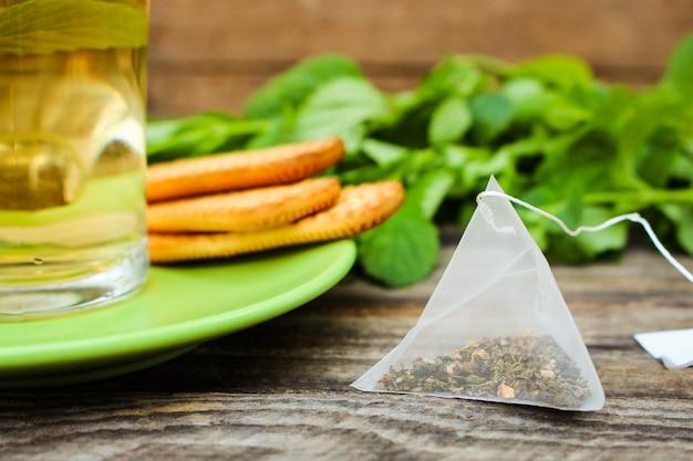 Teebeutel auf hintergrund der minze, des plätzchens und der tasse tee Premium Fotos