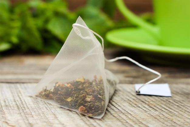 Teebeutel auf hintergrund der minze und und der grünen schale Premium Fotos
