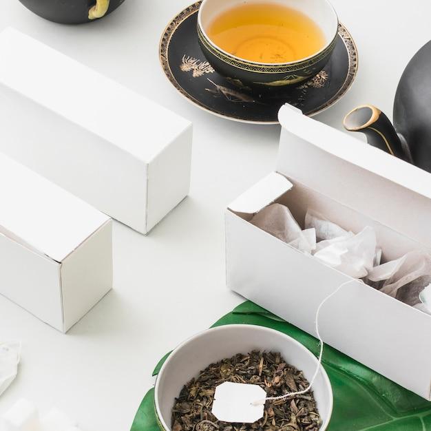Teebeutel im weißen kasten mit kräutertee auf weißem hintergrund Kostenlose Fotos