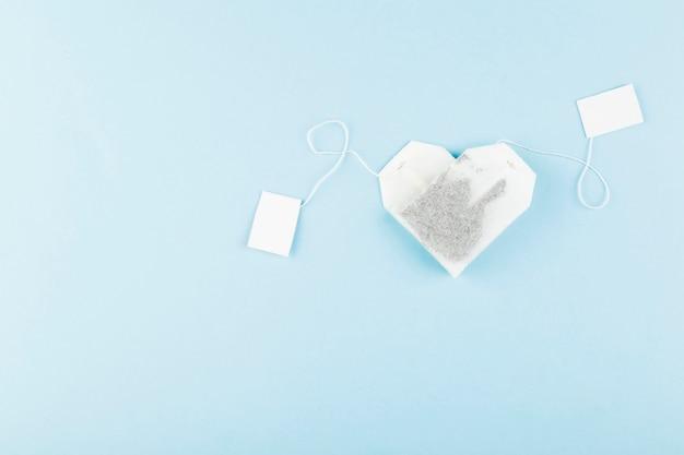 Teebeutel in form von herzen auf blau. draufsicht, exemplar Premium Fotos