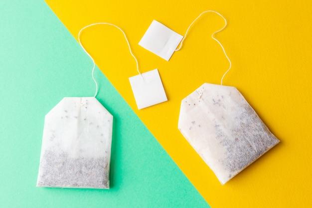 Teebeutel mit weißaufklebern auf einem grünen und hellen gelben pastellhintergrund Premium Fotos