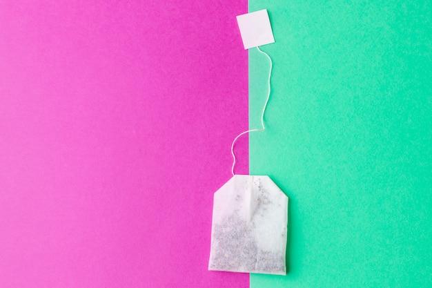 Teebeutel mit weißaufklebern auf einem grünen und hellen rosa pastellhintergrund Premium Fotos