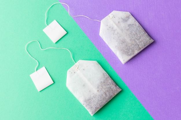 Teebeutel mit weißaufklebern auf einem grünen und purpurroten pastellhintergrund Premium Fotos