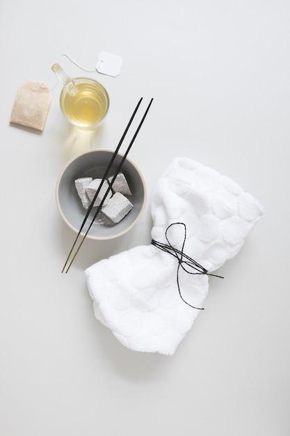 Teebeutel; öl; bimsstein; räucherstäbchen und gebundene serviette auf weiße fläche Kostenlose Fotos