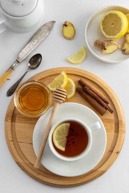 Teecup mit zitrone und honig auf einem weiß. heiße teeschale lokalisiert, draufsichtebenenlage. flach liegen. herbst-, herbst- oder wintergetränk. copyspace. Premium Fotos