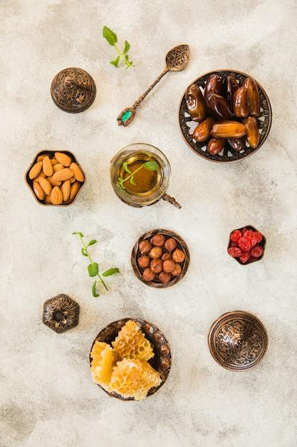 Teeglas mit dattelfrucht und -nüssen auf tabelle Kostenlose Fotos