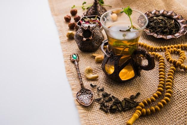 Teeglas mit nüssen, kräutern und perlen auf leinwand Kostenlose Fotos