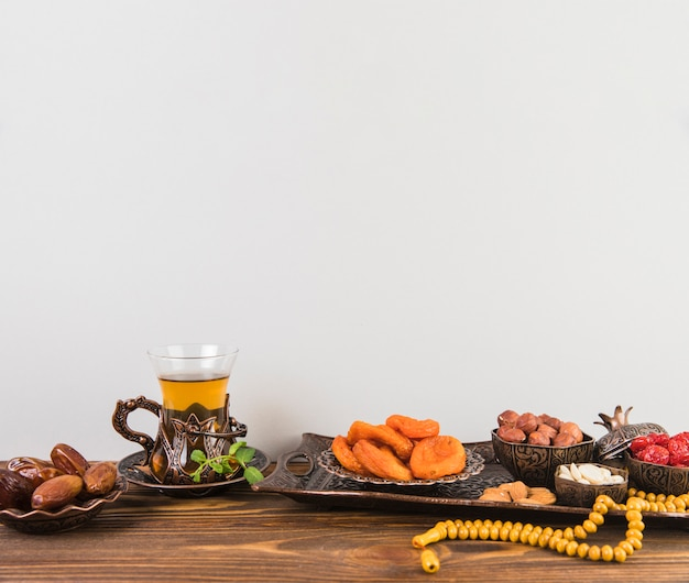 Teeglas mit trockenfrüchten und perlen auf tabelle Kostenlose Fotos