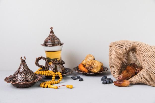 Teeglas mit trockenfrüchten und rosenkranzperlen Kostenlose Fotos