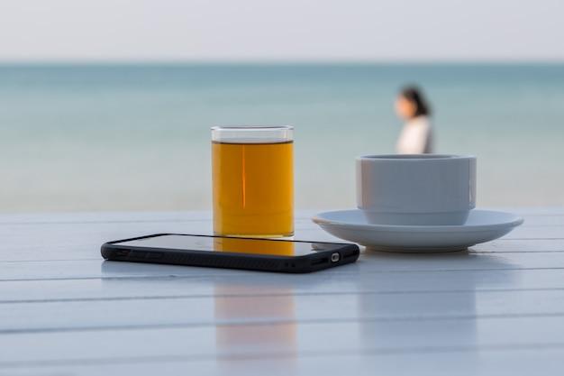Teekaffee mit intelligentem telefon auf dem weißen holztisch am strandhintergrund Premium Fotos