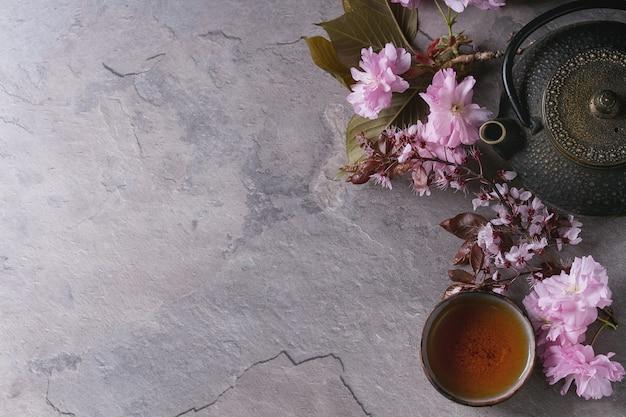 Teekanne und tasse tee mit blütenzweig Premium Fotos